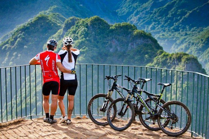 Portugal Urlaub, Mountainbikes, Pärchen steht neben Fahrrädern und bewundert Ausblick